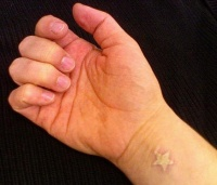 White ink wrist tattoo with small star